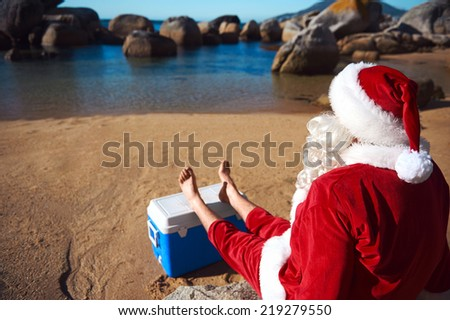 Father Christmas relaxing on the beach resting his bare feet on his cooler while looking at the view - stock photo