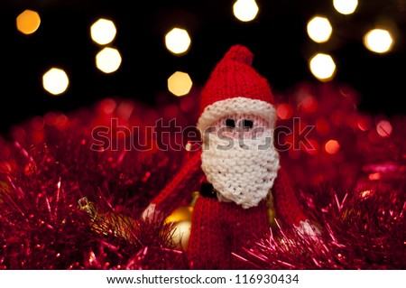Father Christmas Santa Claus toy amidst tinsel and baubles. - stock photo