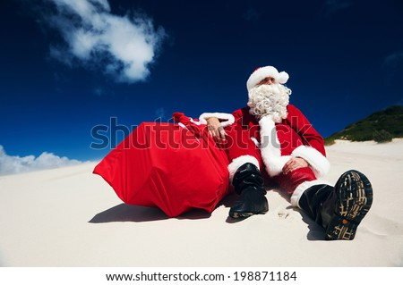 Father Christmas sitting on the beach sand next to his sack of presents - stock photo