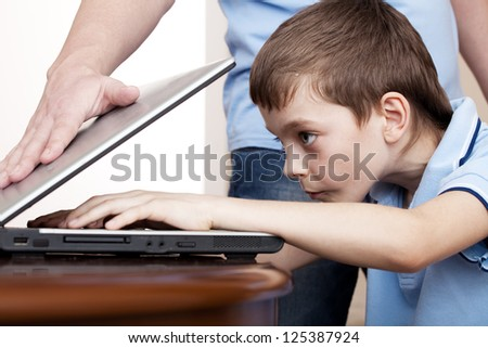 father closes the son's laptop. Computer Addiction. Gambling - stock photo