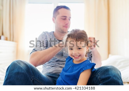 Father combing hair of his daughter in the morning. Young father enjoying time with child. Fathers day with daughter at home. Handsome father with little girl. Happy father and daughter.