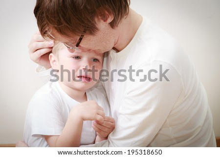 father comforting her crying little son - parenthood concept - stock photo
