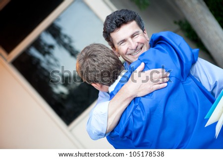 Father congratulating his son on graduation - stock photo