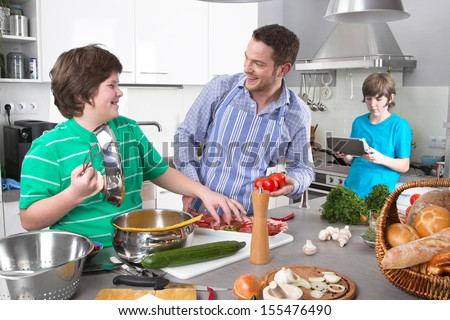 Father cooking with his children in the kitchen - stock photo
