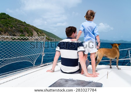 Father, daughter and their pet dog sailing on a luxury yacht or catamaran boat - stock photo