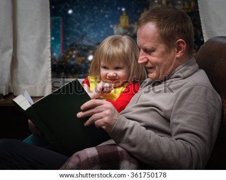 Father daughter reading a book. Dad with his little daughter in a chair by the window. Grandfather and granddaughter. Outside, night city, Moscow. Evening. Winter snow