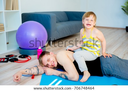 Father doing exercises with daughter