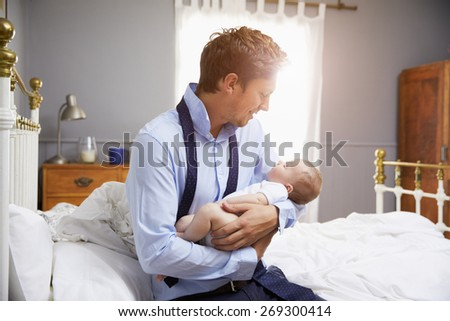 Father Dressed For Work Holding Baby In Bedroom - stock photo
