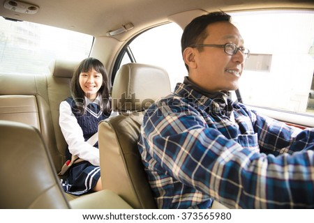 father driving to school with teen daughter - stock photo