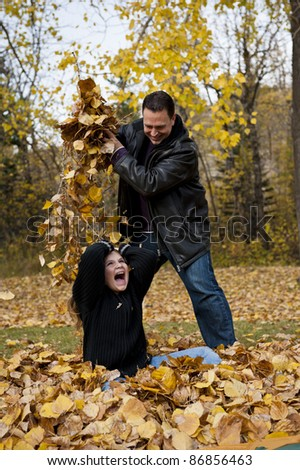 Father dropping a handful of leaves on his daughter while playing