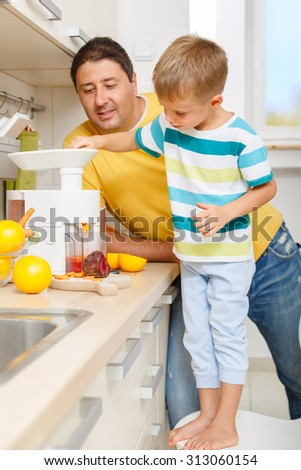 Father educating his little son on healthy diet and making organic juice in the kitchen