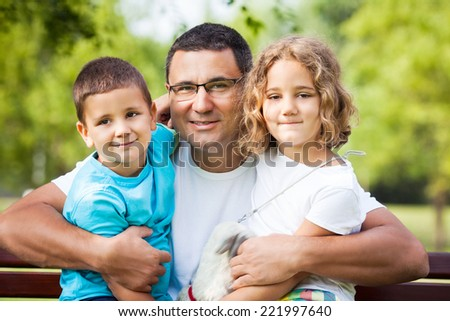 Father embracing his cute little children while sitting on a bench in nature - stock photo
