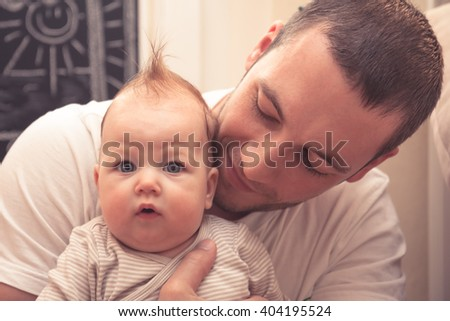 Father embracing his little baby. Father is looking on baby, baby is looking on camera. Baby with funny haircut - stock photo