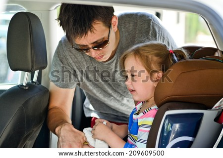 father  fastening  crying  daughter   in car - stock photo