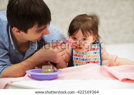 Father feeding baby girl on blanket at home - stock photo