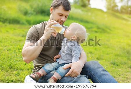 Father feeding baby outdoors - stock photo