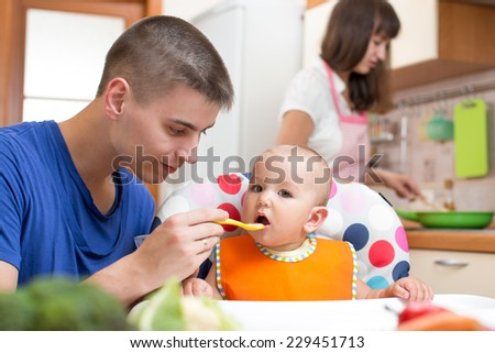 father feeding his baby girl and mother cooking at kitchen