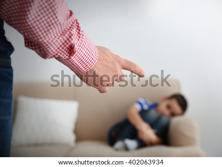 Father fist as punishment and little boy lying on sofa indoors - stock photo