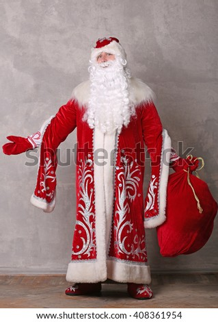 Father Frost in red coat with bag of Christmas gifts - stock photo