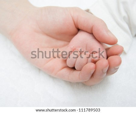 father gently hold a newborn baby's hand