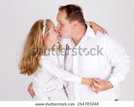 Father gives a sweet kiss on the nose of his adorable little daughter. - stock photo