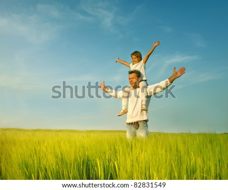 Father gives her daughter piggyback at sunset - stock photo