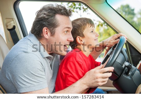Father gives his son driving lessons, enjoying time together - stock photo
