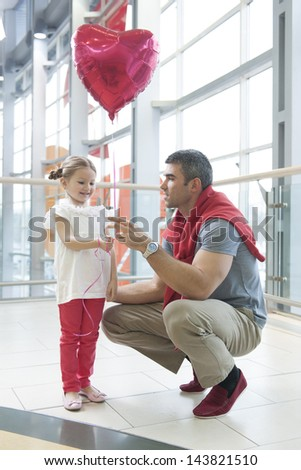 Father gives young daughter heart shaped balloon - stock photo
