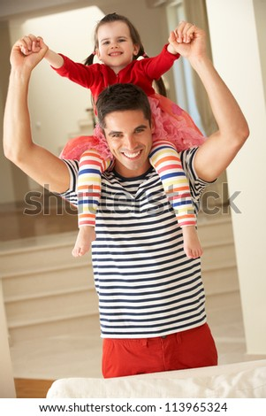 Father Giving Daughter Ride On Shoulders At Home - stock photo