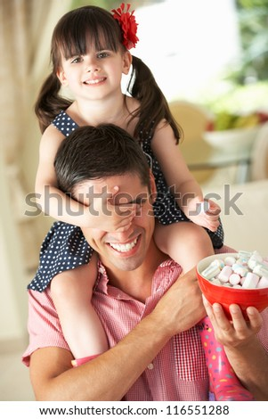 Father Giving Daughter Ride On Shoulders Indoors Whilst Eating Marshmallows - stock photo