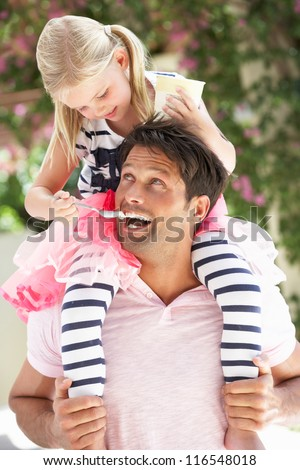 Father Giving Daughter Ride On Shoulders Whilst Being Fed Ice Cream - stock photo