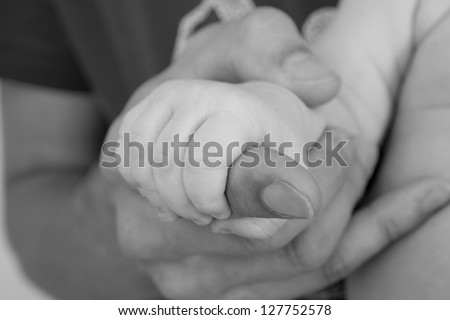 father giving hand to a child, black and white - stock photo