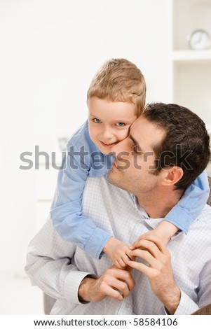 Father giving his son piggiback ride, smiling. - stock photo