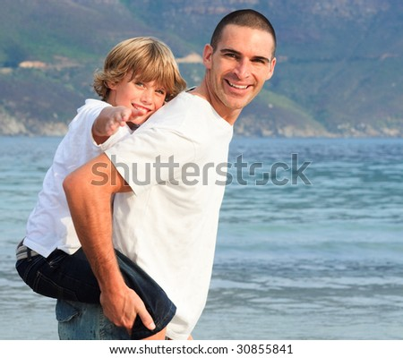 Father giving his son piggyback ride on the beach smiling - stock photo