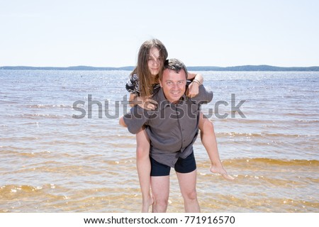 father giving piggyback ride daughter on beach