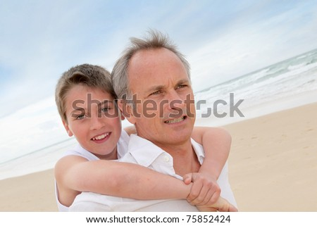 Father giving piggyback ride to son at the beach - stock photo
