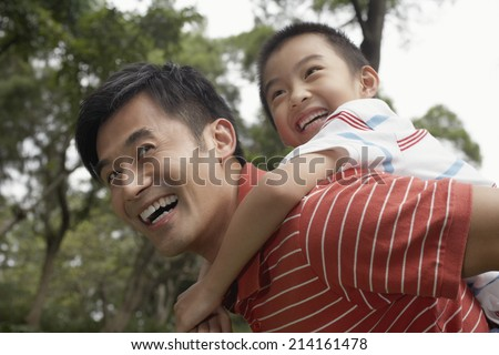 Father giving son piggyback (7-9) in park - stock photo