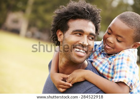 Father Giving Son Piggyback Ride In Park - stock photo