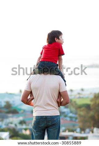Father giving son piggyback ride outdoors - stock photo