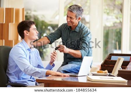 Father Giving Teenage Son Car Keys - stock photo