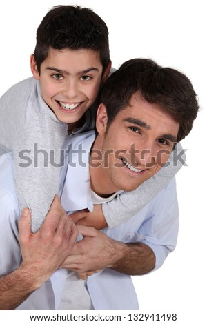 father giving young son piggyback - stock photo