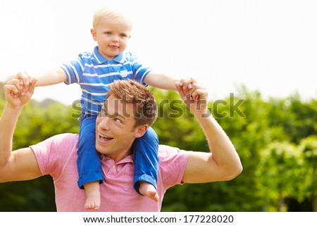 Father Giving Young Son Ride On His Shoulders In Garden - stock photo