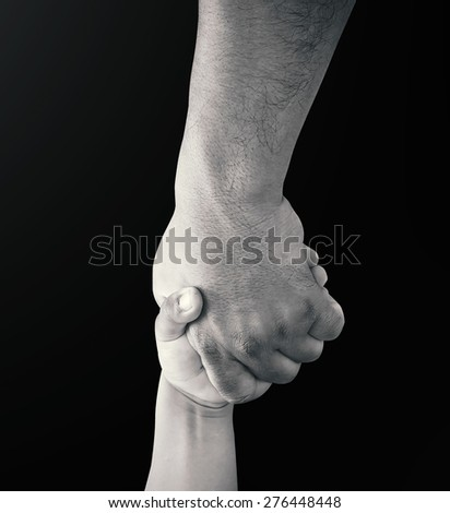 Father hand holding child hand over black background. - stock photo