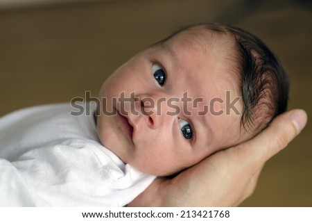 Father hand holding his newborn. Baby looking adorable with his big black eyes and relaxing