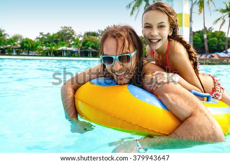 Father having fun with her tween daughter on the inflatable ring in the water park together
