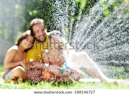 Father having fun with his little sons holding water sprinkler