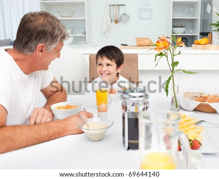 Father having his breakfast with his son at home - stock photo