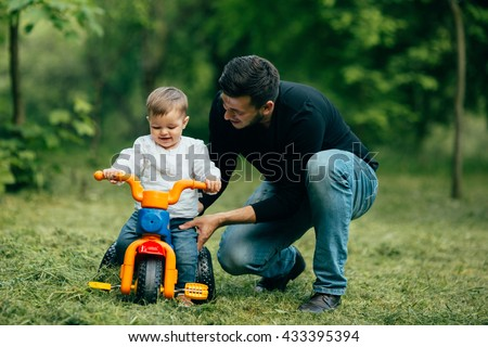 Father help his child to ride on bicycle - stock photo