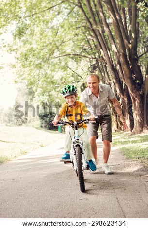 Father help his little son ride bicycle - stock photo