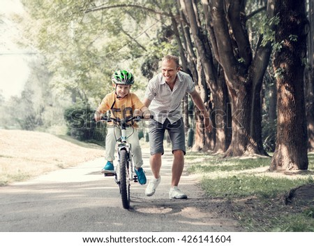 Father help his son learn to ride bicycle - stock photo